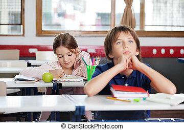 Schoolgirl Writing Notes In Classroom - Little school girl...