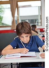 Schoolboy Cheating At Desk During Examination - Schoolboy...