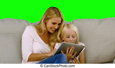 Mother and her daughter using digital tablet in slow motion...