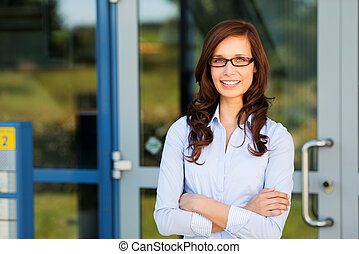 Woman standing outside her house and smiling