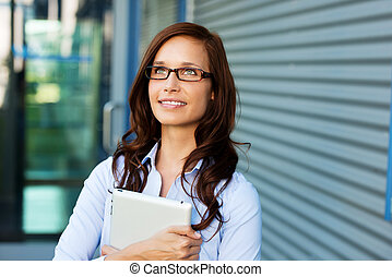 Beautiful lady thinking and holding a tablet