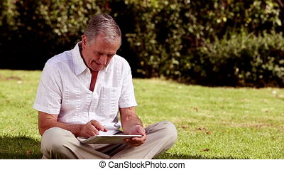 Mature man sat on the grass using his tablet computer in a...