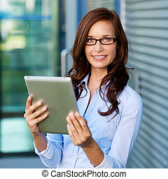 Casual woman browsing the internet through her ipad outdoors