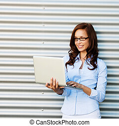 Woman standing and checking mails on laptop - Image of a...