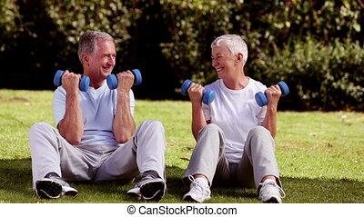 Mature couple sat on the grass lifting dumbbells in a park