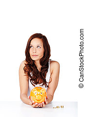 Woman holding a piggy bank and daydreaming of all the things...