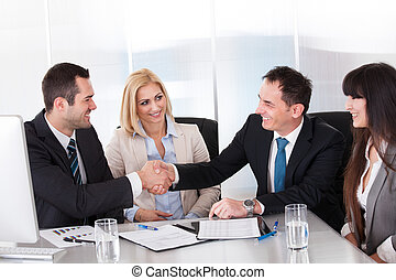 Two Businessman Shaking Hands In front Of Colleges