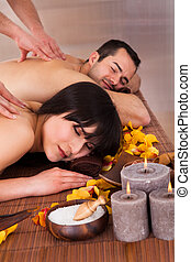 Beautiful Young Couple Enjoying Massage In Spa Centre