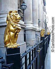 Lion statues on gate railings - Small golden lion statues on...