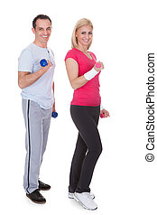 Portrait Of Couple Exercising With Dumbbells - Happy Couple...