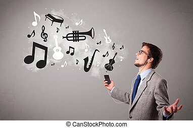 attractive young man singing and listening to music with...