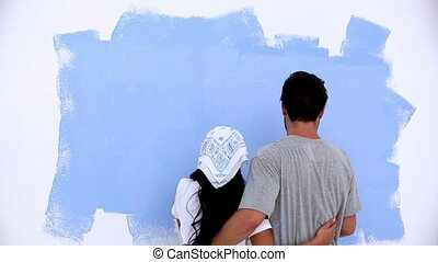 Lovely couple painting a wall in blue