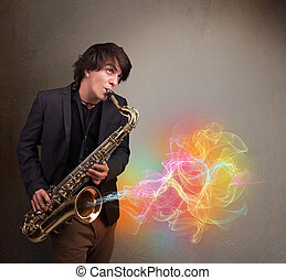 Attractive young musician playing on saxophone with colorful...