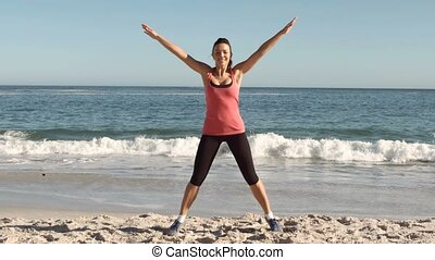 Happy woman working out on the beach in slow motion