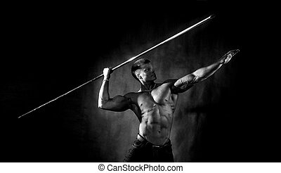 Bodybuilder throwing javelin - Side view of muscular...