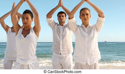 Group of people practicing yoga on the beach in slow motion