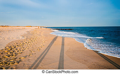 Long evening shadows on the beach at Cape May, New Jersey. -...