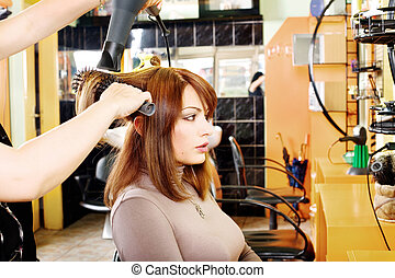 hairdresser makes a hair dress to the young brunette...