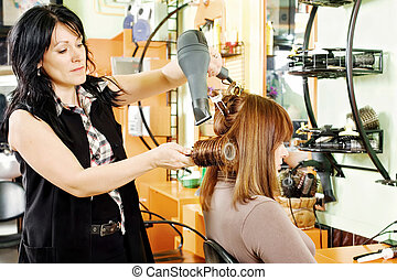 hairdresser drying customer's hair - professional...