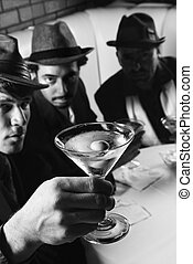 Retro men drinking martinis. - Three Caucasian prime adult...