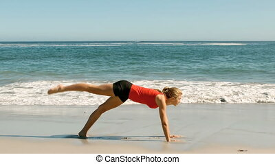 Woman doing exercises at the beach