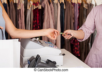 Customer Receiving Credit Card From Saleswoman - Female...