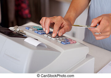 Saleswoman Holding Credit Card While Using Cash Desk -...