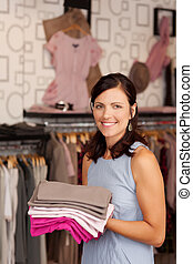 Saleswomen Holding Stack Of Clothes In Boutique - Portrait...
