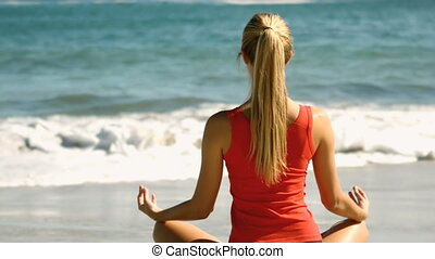 Woman meditating on the beach in slow motion