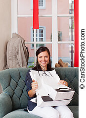 Portrait of smiling woman with shopping bags sitting on sofa at clothing store