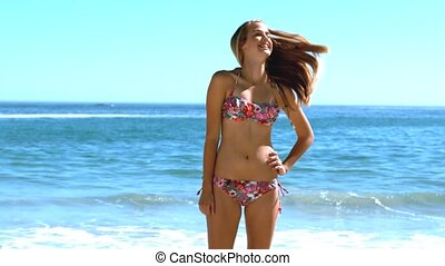 Young woman tossing her hair on the beach in slow motion