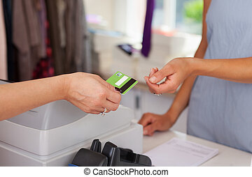 Closeup Of Saleswoman Giving Credit Card To Customer -...