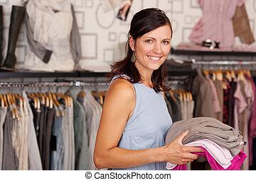 sonriente, mujer, tenencia, Pila, de, ropa, en, Boutique