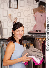 Pretty Customer Holding Stack Of Clothes In Boutique -...