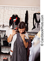 Woman With Shopping Bags Trying Dress In Store - Mid adult...