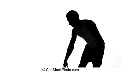 Silhouette of a man throwing a basketball on white...