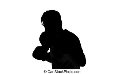 Silhouette of a man boxing on white background in slow...