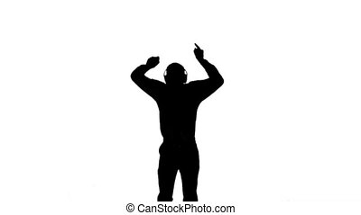 Silhouette of a man enjoying music and jumping on white...