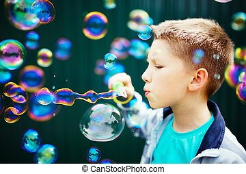 Kid making soap bubbles outside