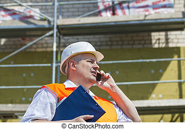 Construction Manager talking on the phone near the...