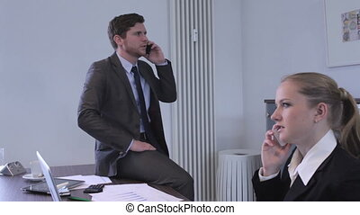Business man and woman in an office both talking on their...