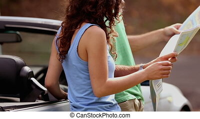 Couple reading map on side of the road and talking