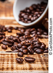 Coffe beans with blured coffe cup
