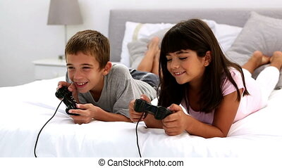 Two children playing video games lying on a bed
