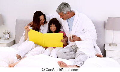 Parents and their daugher reading book lying on the bed