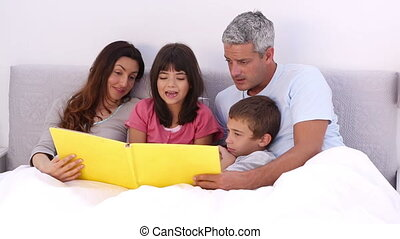 Family reading a story in bed