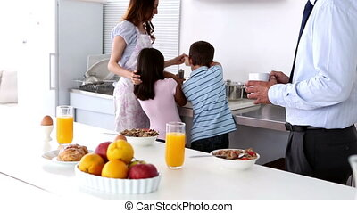 Mother and her children cooking on the kitchen with father...