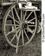 Western Implements - Antique rifle along wagon wheel with...
