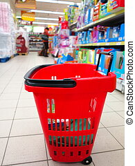 shopping basket with grocery at supermarket - view of a red...
