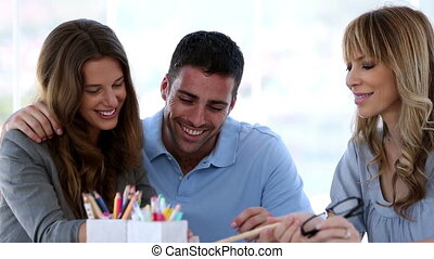 Couple with their interior designer in creative office